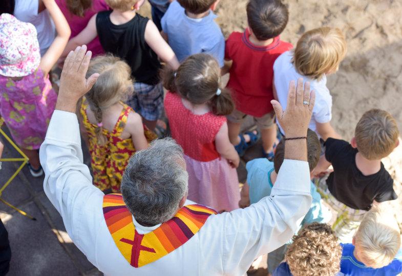 Zum Segen breitet ein Priester seine Hände über Kindergartenkinder aus