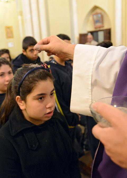 Am Aschermittwoch streut ein Priester einem Mädchen Asche auf den Kopf