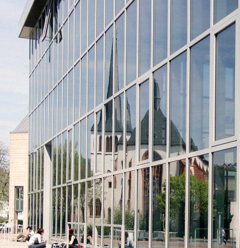 Ein spätgotischer Kirchenbau spiegelt sich in einer postmodernen Glasfassade