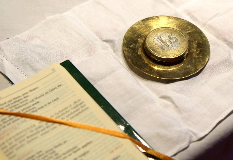 Pyxis auf einem Korporale, daneben ein aufgeschlagenes Schott-Messbuch