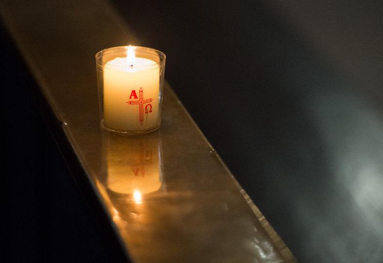 Eine brennende Kerze mit Kreuz und Alpha-Omega-Symbolen steht auf einer Kirchenbank