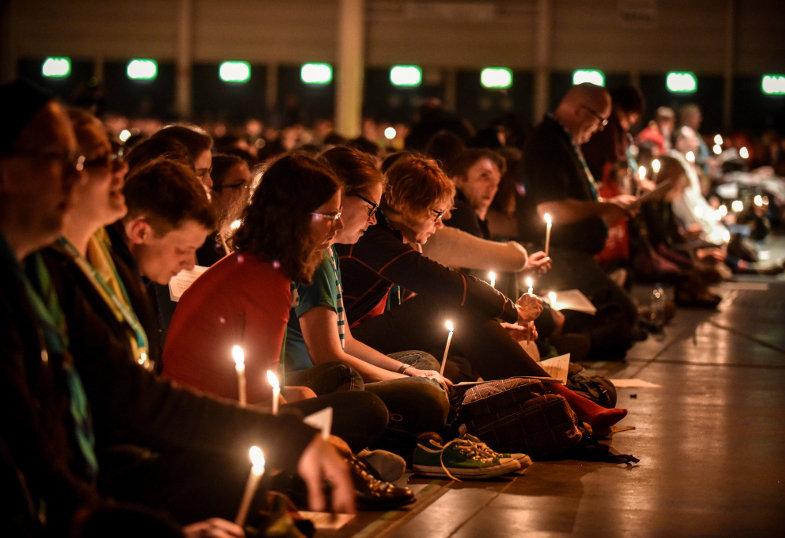 Betende mit brennenden Kerzen in einer dunklen Kirche