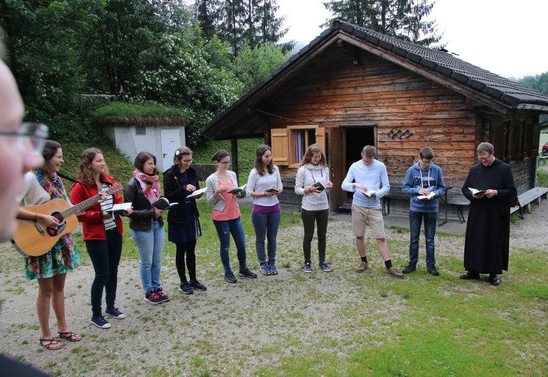 Jugendliche beten im Halbkreis auf einer Wiese