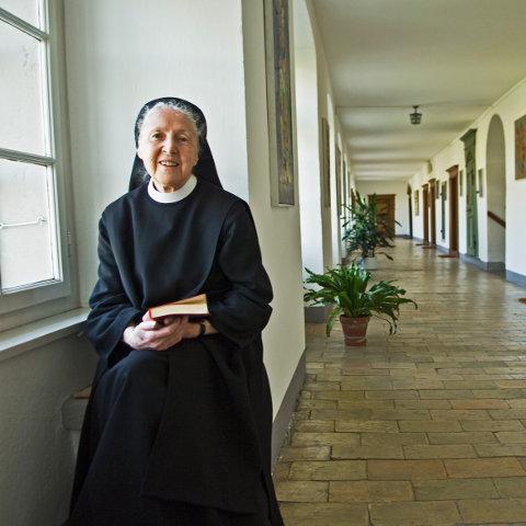 Die Benediktinerin Silja Walter mit Buch in der Hand an einem Fenster