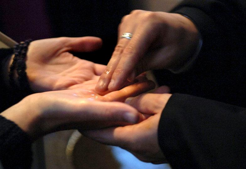 Bei einem Tauferinnerungsgottesdienst zeichnen zwei Teilnehmer einander mit Weihwasser ein Kreuz in die Hand