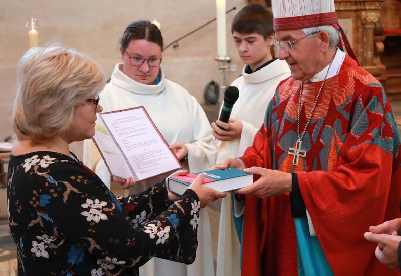 Ein Weihbischof überreicht eine Bibel an eine neugesendete Gemeindereferentin