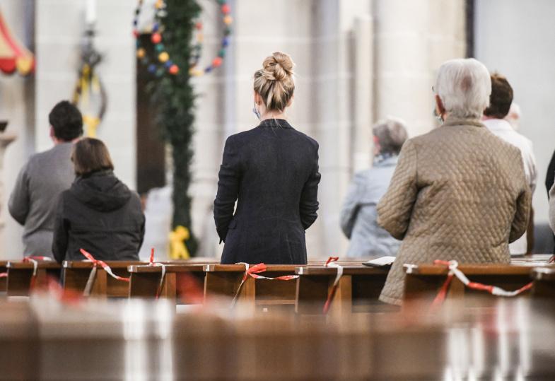 Gottesdienstfeiernde mit Mundschutz in Kirchenbänken mit Absperrband