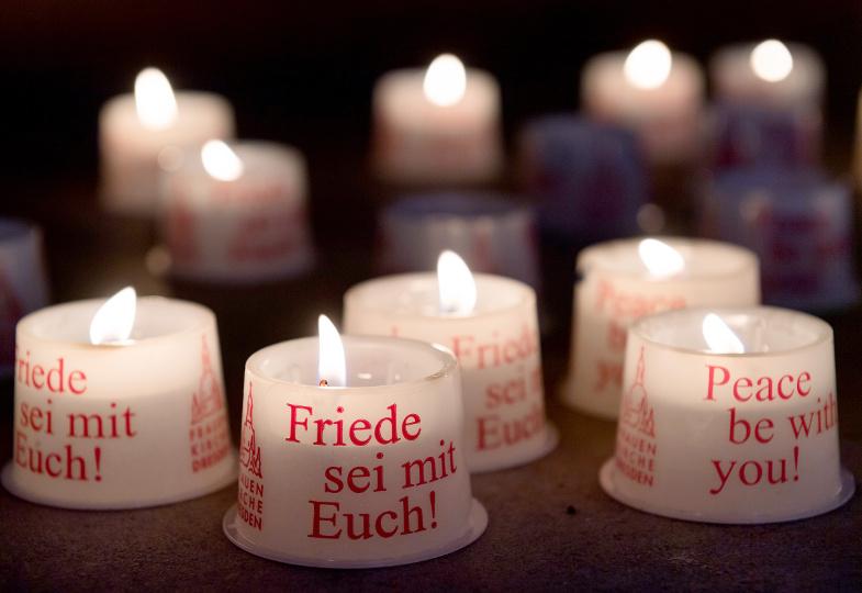 Brennende Kerzen mit aufgedrucktem Friedenswunsch