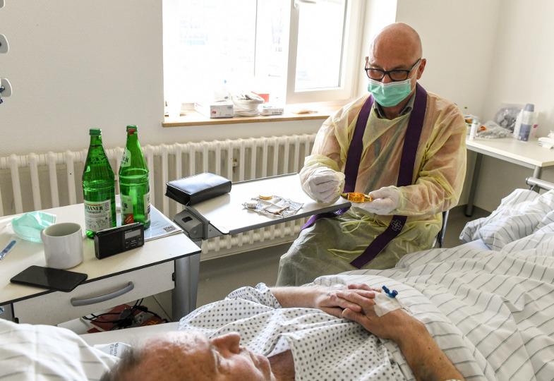 Ein Priester in klinischer Schutzkleidung spendet einem Patienten die Krankenkommunion