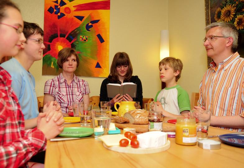 Eine Familie betet am Frühstückstisch