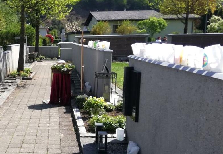 Windlichter stehen um ein Grab