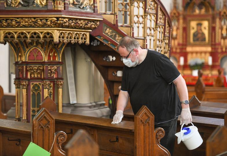 Ein Sakristei desinfiziert eine Kirchenbank