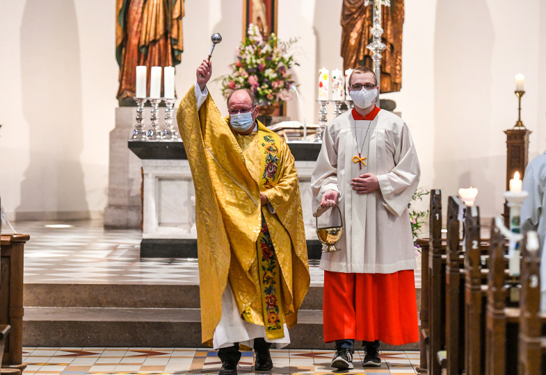 Ein Priester sprengt beim Taufgedächtnis Weihwasser über Gläubige.