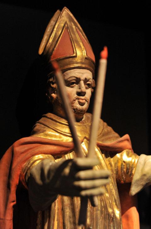 Eine Statue des heiligen Blasius hält zwei gekreuzte Kerzen in der Hand