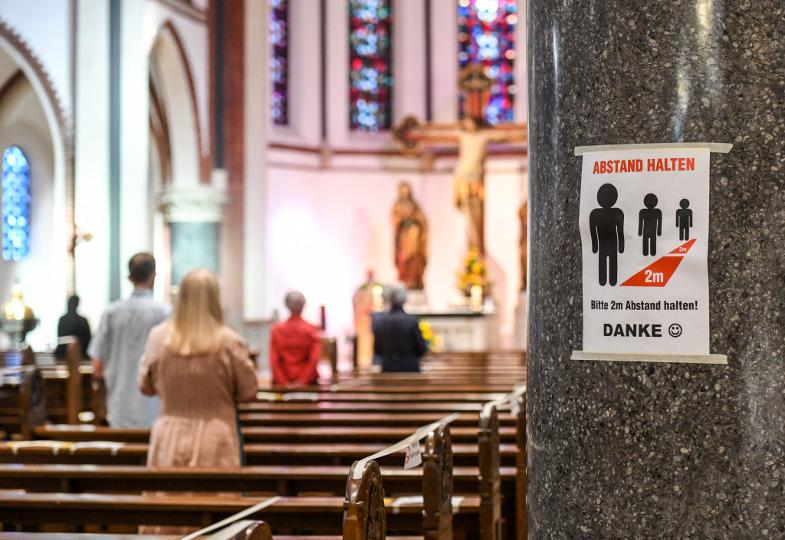Ein Kirchenraum mit Absperrband an den Bänken und einem Hinweisschild zum Abstandhalten