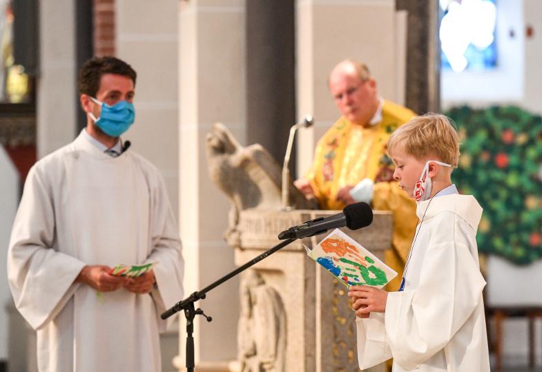 Ein Erstkommunionkind liest mit abgelegter Mund-Nase-Bedeckung eine Fürbitte vor