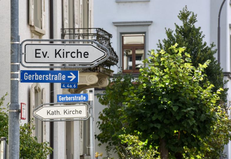 Zwei Straßenschilder weisen - in entgegengesetzter Richtung - den Weg zu einer evangelischen und einer katholischen Kirche.