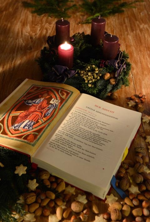 Ein aufgeschlagenes Evangeliar vor einem Adventskranz mit brennender erster Kerze