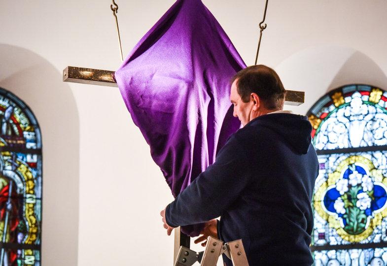 Ein Sakristan verhüllt ein Kruzifix mit einem violetten Tuch