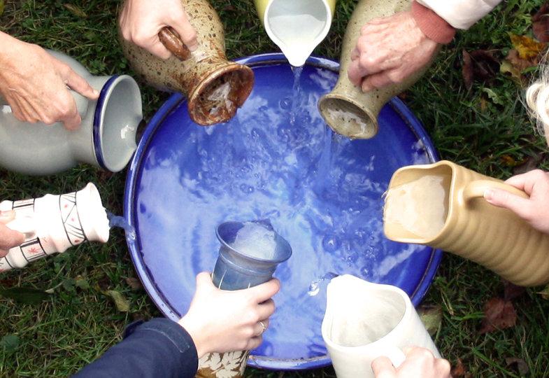 Verschiedene Menschen gießen Wasser aus unterschiedlichen Krügen in eine große Schale, die überläuft