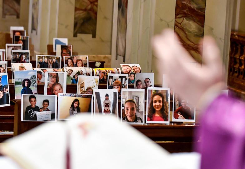 Während der Corona-Pandemie sind Selfies der Gläubigen in den leeren Kirchenbänken angebracht, während der Priester Eucharistie feiert