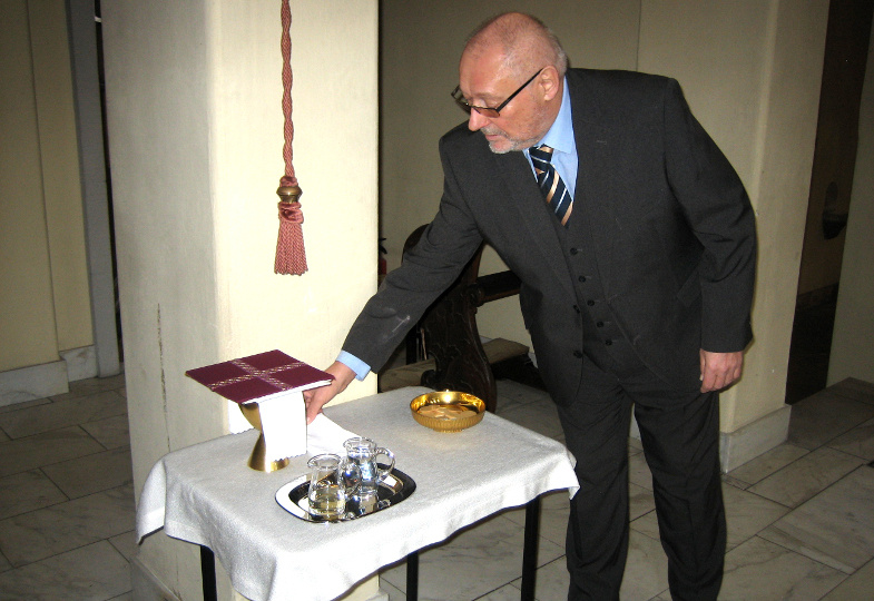 Ein Küster stellt auf der Kredenz die Gaben und Geräte für die Eucharistiefeier bereit