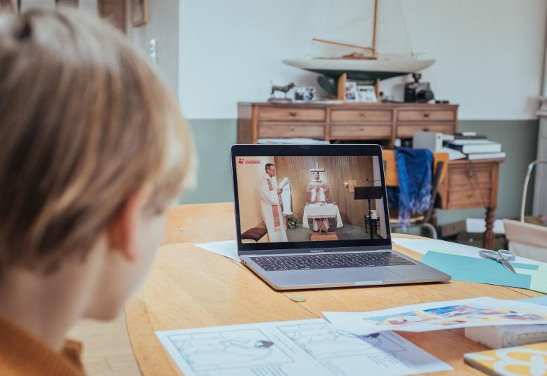 Ein Kind schaut am Laptop eine gestreamte Eucharistiefeier.