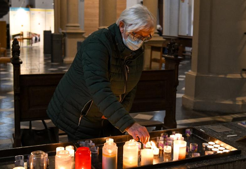 Eine Frau mit Mundschutz entzündet eine Kerze