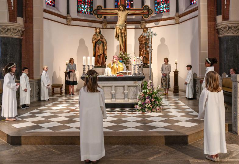 Erstkommunionkinder stehen in Abstand um den Altar.