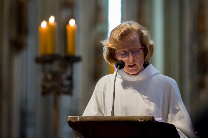 Eine Lektorin in liturgischem Gewand verkündet eine Lesung