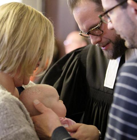 Eltern halten ihr Baby für den Segenszuspruch durch einen Geistlichen