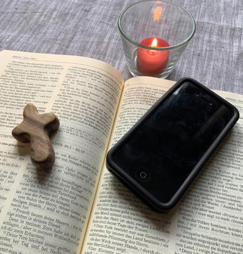 Aufgeschlagene Bibel, darauf ein Kreuz und ein Smartphone, daneben eine brennende Kerze