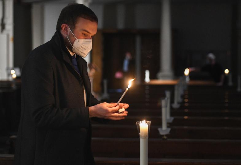 In einer dunklen Kirchen werden Kerzen entzündet.