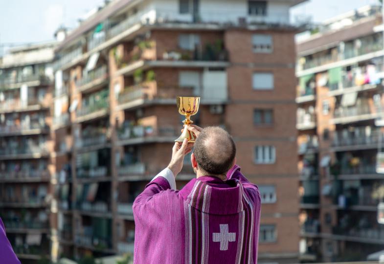 Mit Blick auf Hochhäuserfassaden erhebt ein Priester den Kelch