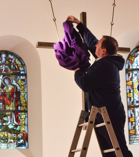 Ein Küster steht auf einer Leiter und verhüllt das Kreuz in einer Kapelle mit einem violetten Tuch.