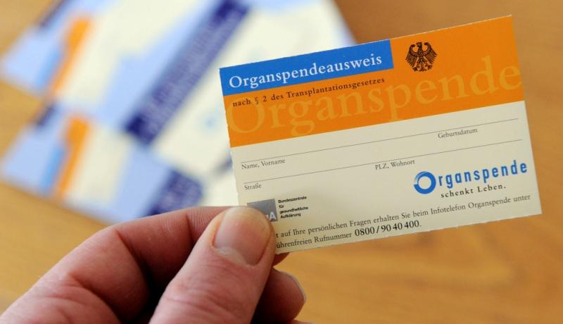 Hand hält Organspendeausweis