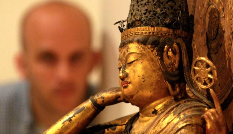 Mann betrachtet Buddha-Figur