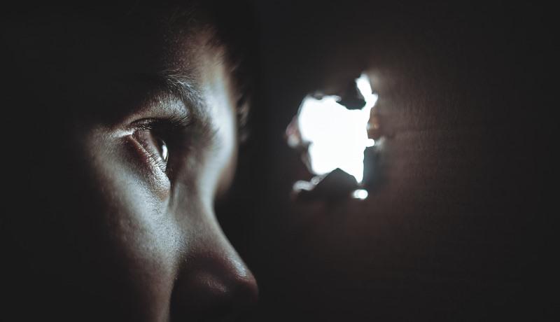 Kind schaut durch ein Loch in der Wand aus dem Dunkeln ins Helle