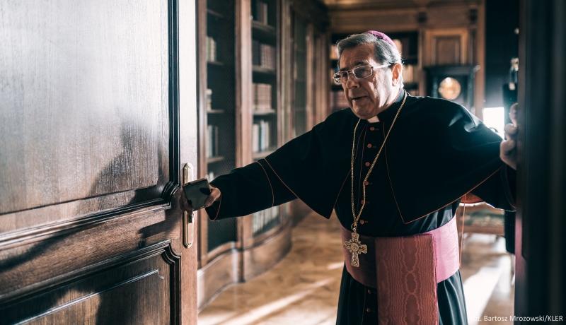 Erzbischof steht an geöffneter Holztür
