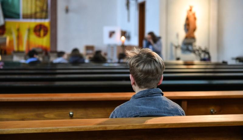 Ein Junge sitzt in einer Kirchenbank.