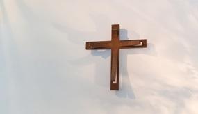 Kreuz hängt an Wand