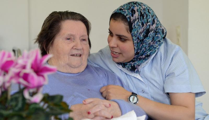 Muslima mit Kopftuch kümmert sich um alte Frau