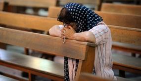Irakische Christin betet in einer Kirchenbank