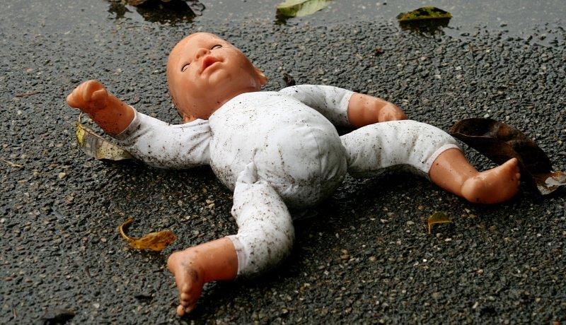 Puppe liegt im Straßendreck