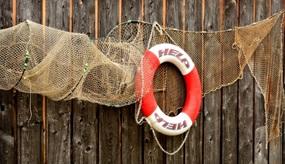 Fischernetz und Rettungsring vor Holzwand