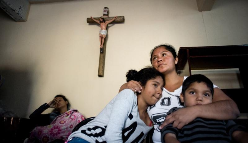 Geflüchtete Mutter umarmt ihre Kinder unter einem Kreuz