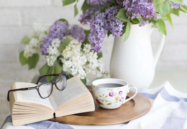 Ein Buch, eine Tasse Kaffee und Blumen auf einem Tisch