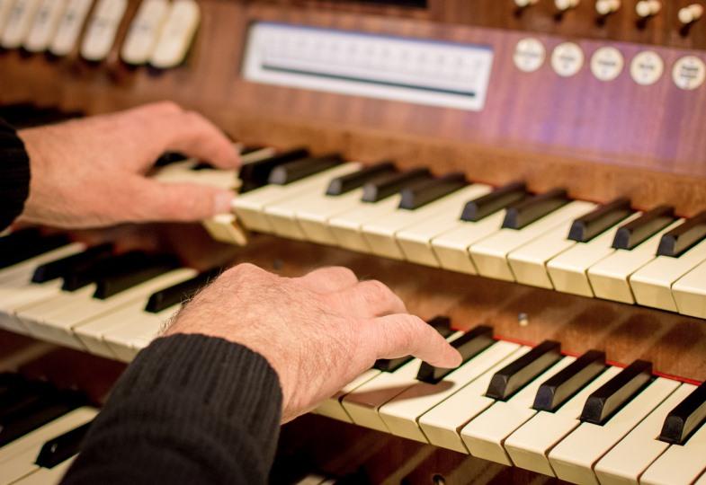 Jemand sitzt an der Orgel.