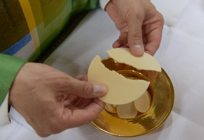 Priester bricht das Brot.
