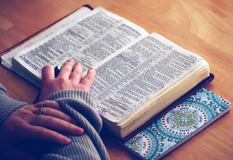 Eine Frau liest in einer Bibel.
